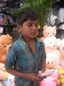 Young boy selling soft toys