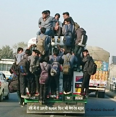 People hanging from a bus in a city in India