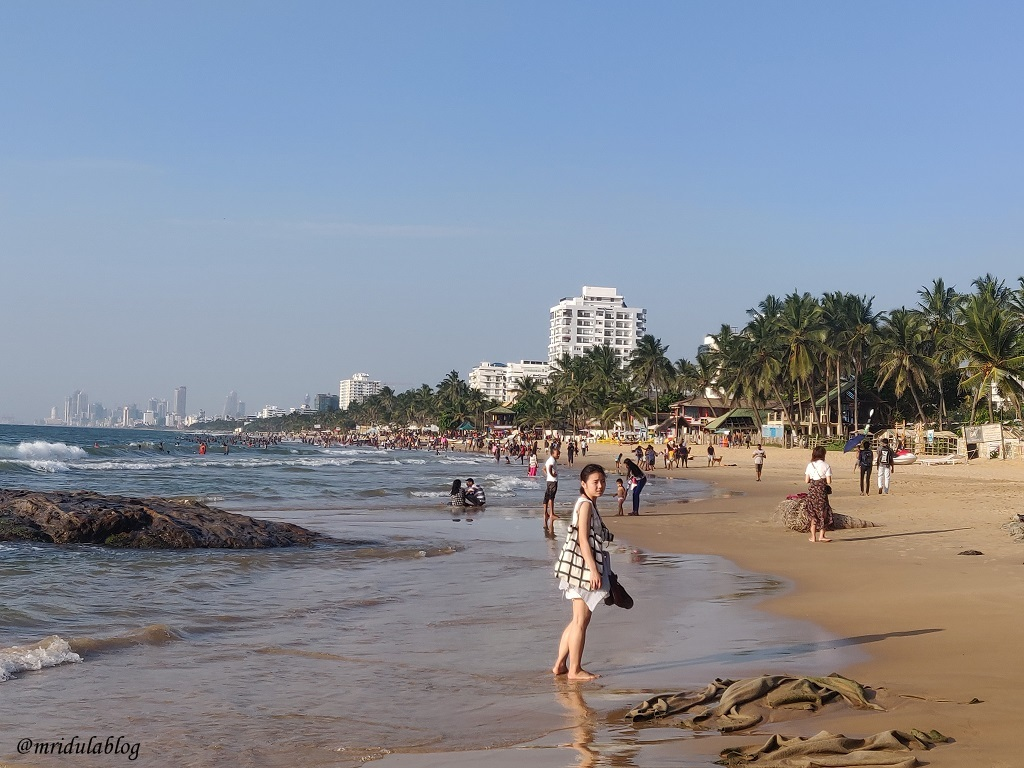 Tourists at Mt. Lavinia beach in Sri lanka with Colombo Skyline visible in far distance